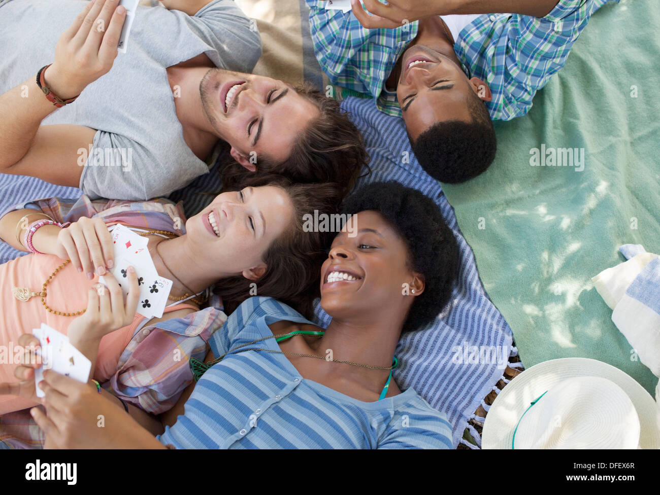 Friends playing cards on blankets outdoors - Stock Image