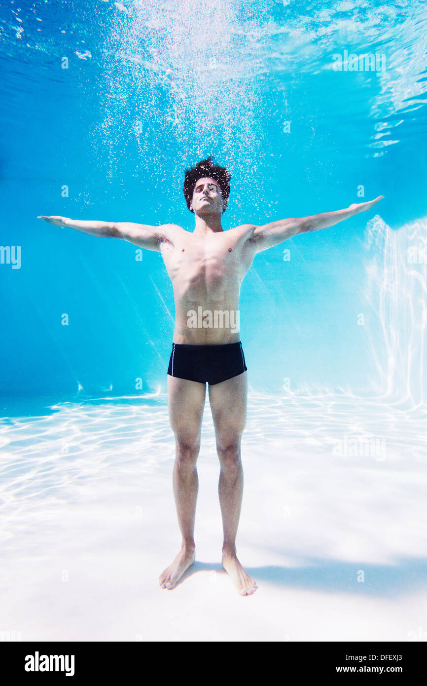 Man standing underwater in swimming pool with arms outstretched - Stock Image