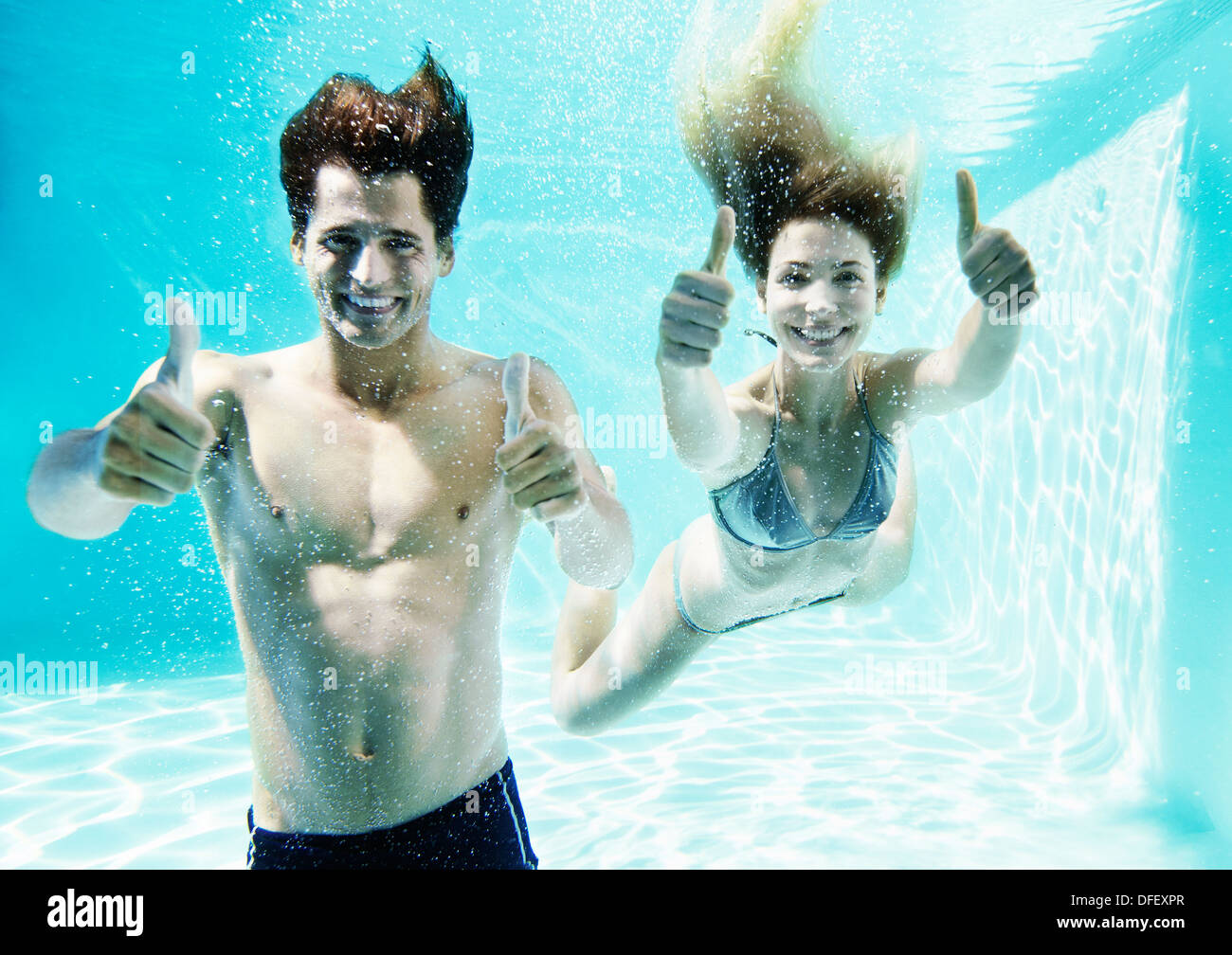 Couple giving thumbs up underwater in swimming pool - Stock Image