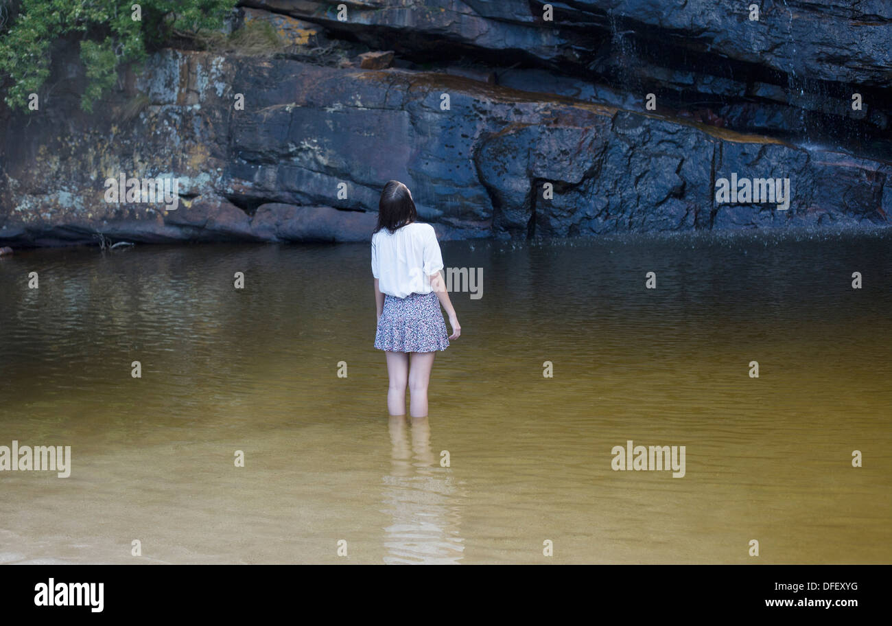 Woman wading and looking up in pool - Stock Image