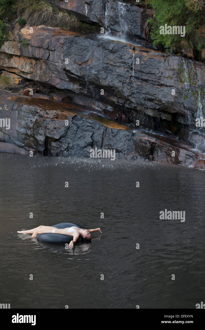 Woman floating in inner tube on river - Stock Image