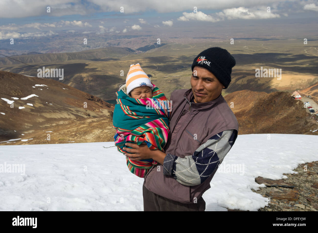 Bolivian father carrying his newborn child to the 5421 metre (17,785 ft) summit of Chacaltaya as a local tradition, showing the remnants of the Chacaltaya Glacier, near La Paz, Bolivia - Stock Image