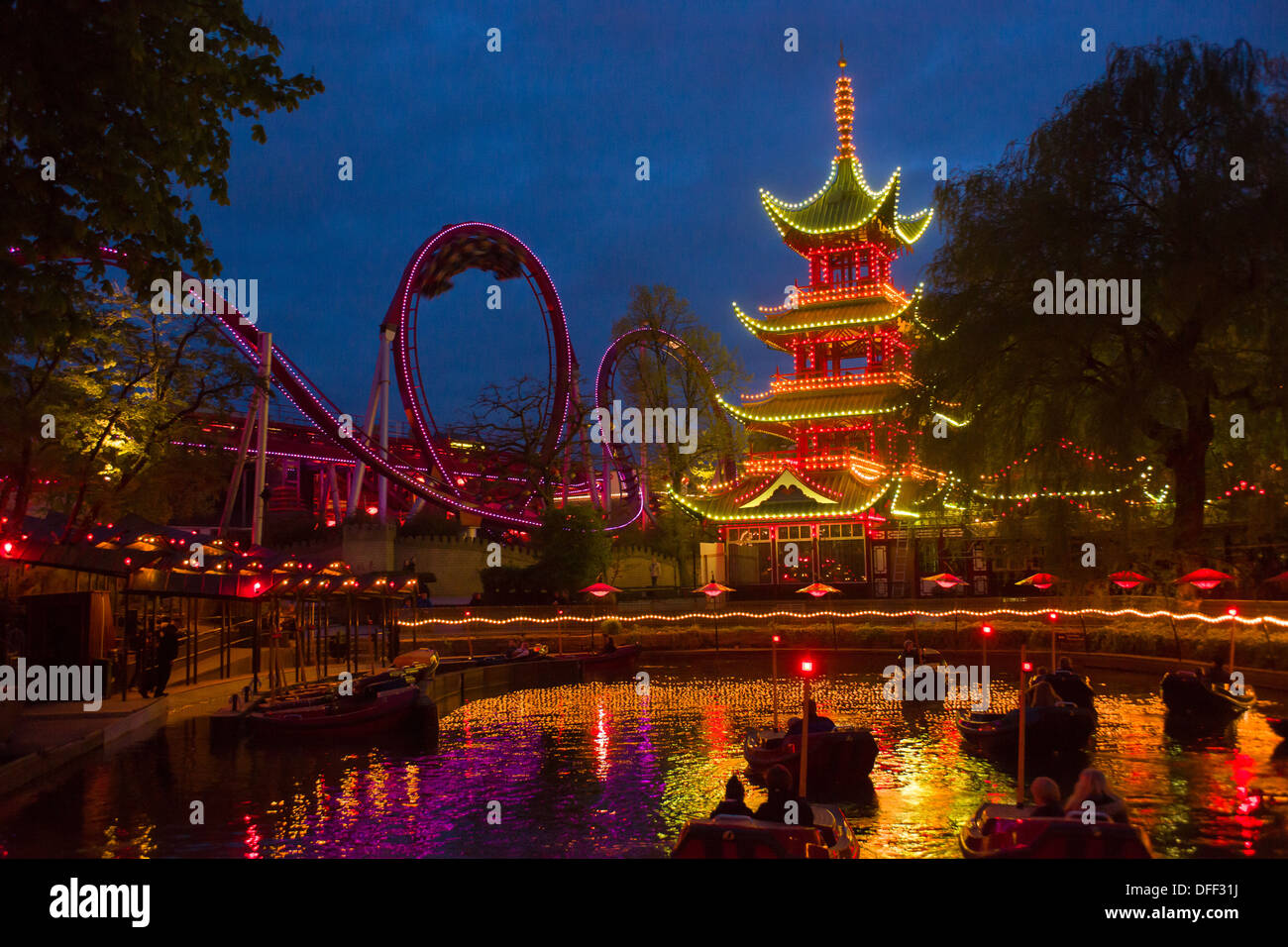 Boating lake in front of the floodlit Chinese Pagoda and Rollercoaster at night, Tivoli Gardens, Copenhagen, Denmark - Stock Image