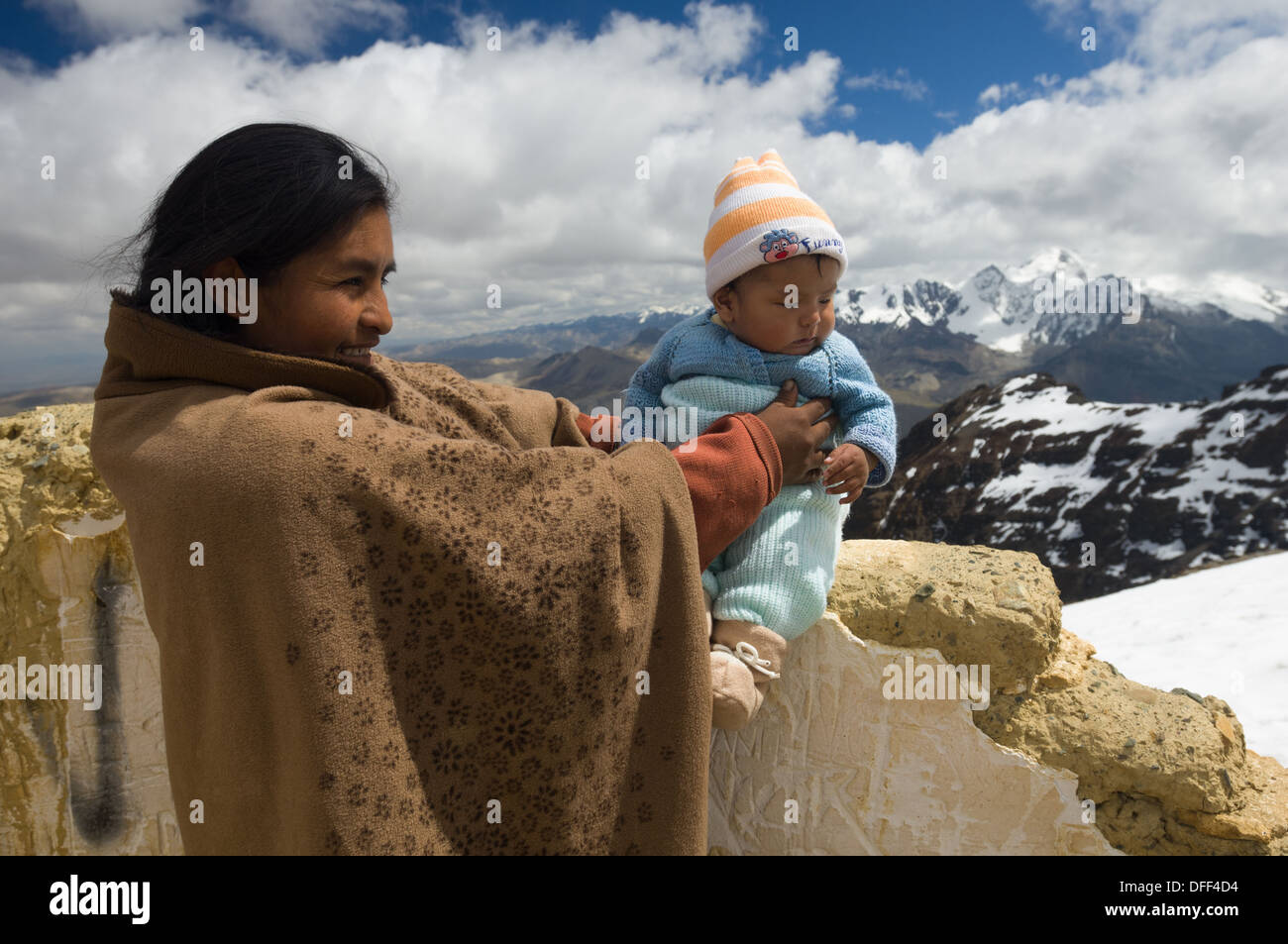 Bolivian mother holding her newborn child at the 5421 metre (17,785 ft) summit of Chacaltaya, as a local tradition, near La Paz, Bolivia - Stock Image