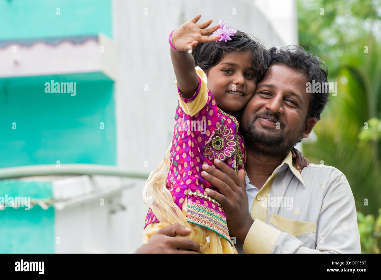 Indian Father and Daughter waving and smiling. Andhra Pradesh, India - Stock Image