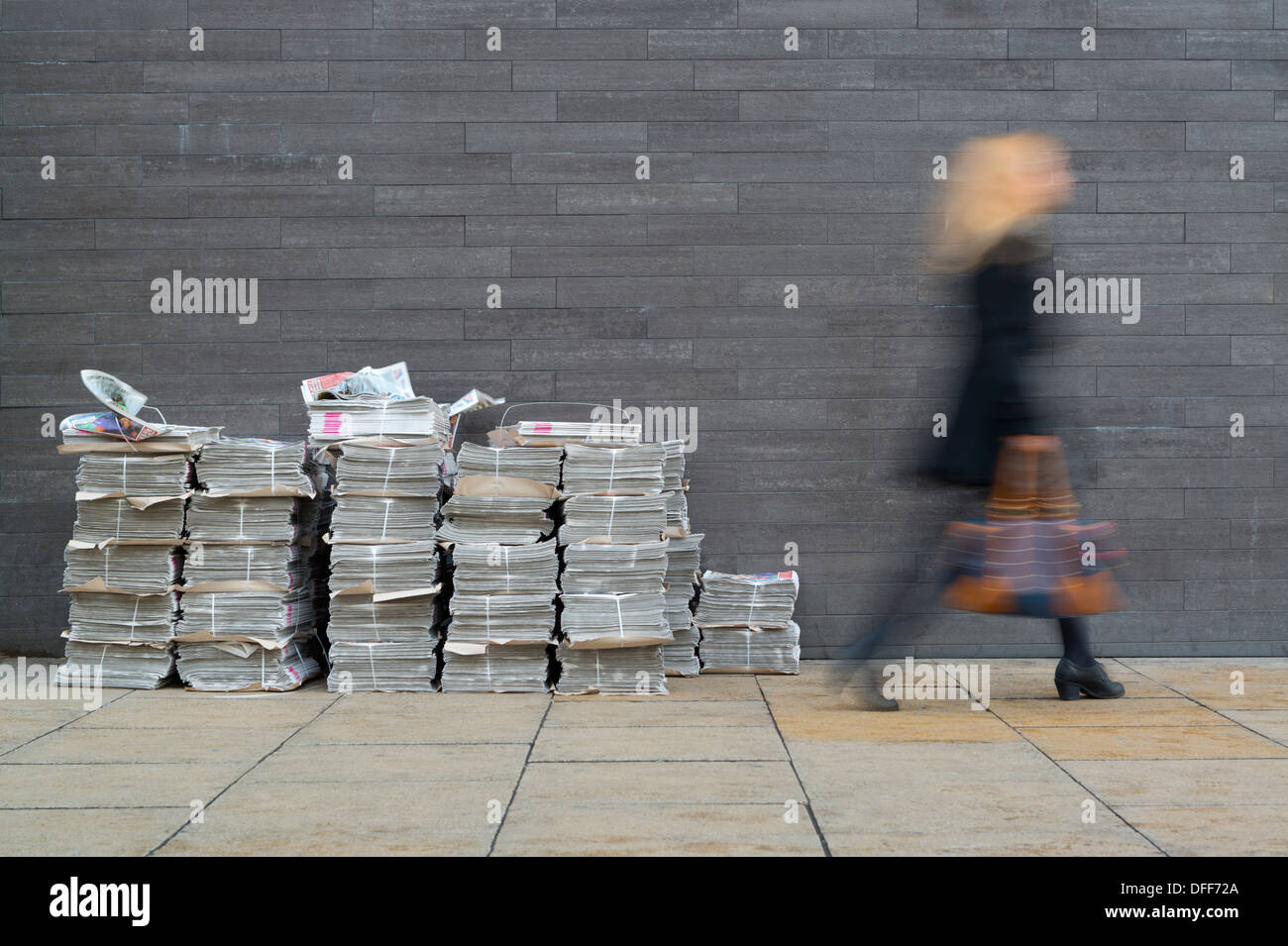 Woman walks past stacks of free Metro newspaper during morning rush hour in Manchester. - Stock Image