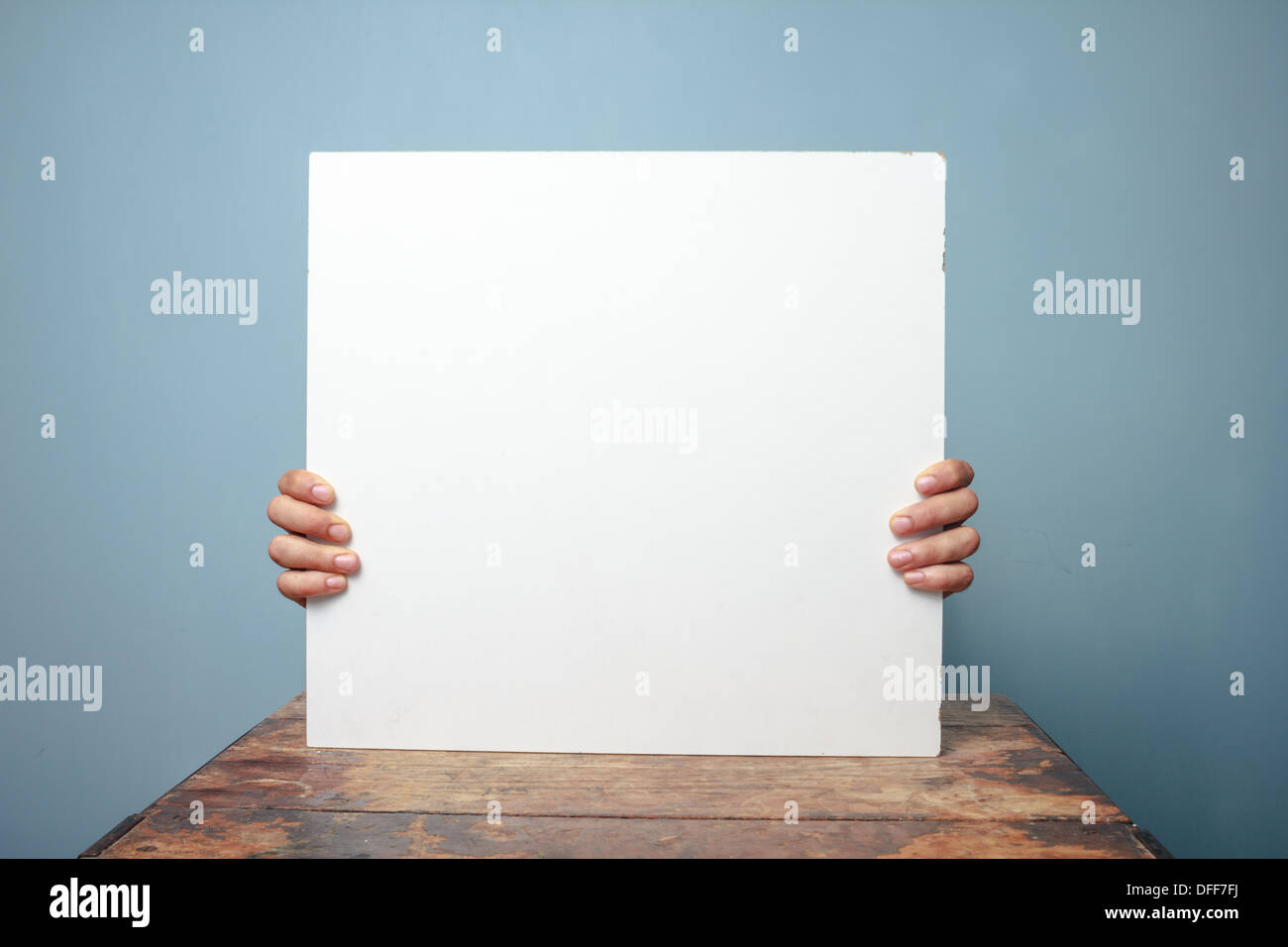 Young man sitting at a table and holding a blank white sign, only his fingers are visible - Stock Image