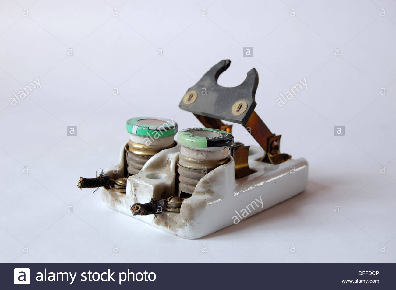 1950s vintage ceramic fuse box electrical circuit breaker with fuses and  knife switch plain background natural light closeup