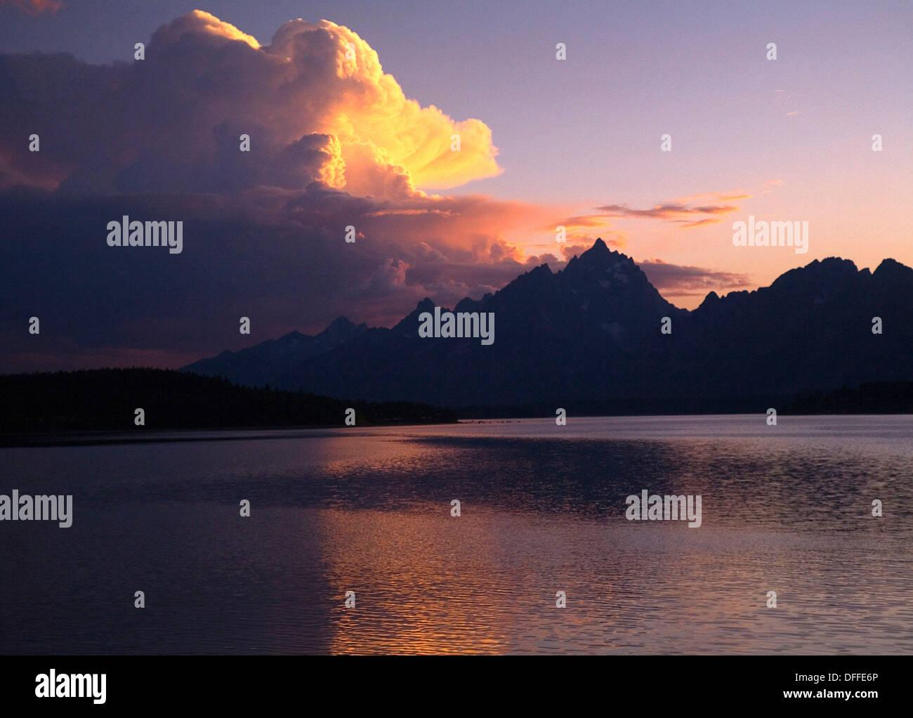 The setting sun shines over The Tetons Mountain Range and Jackson Lake at Grand Teton National Park, Wyoming - Stock Image