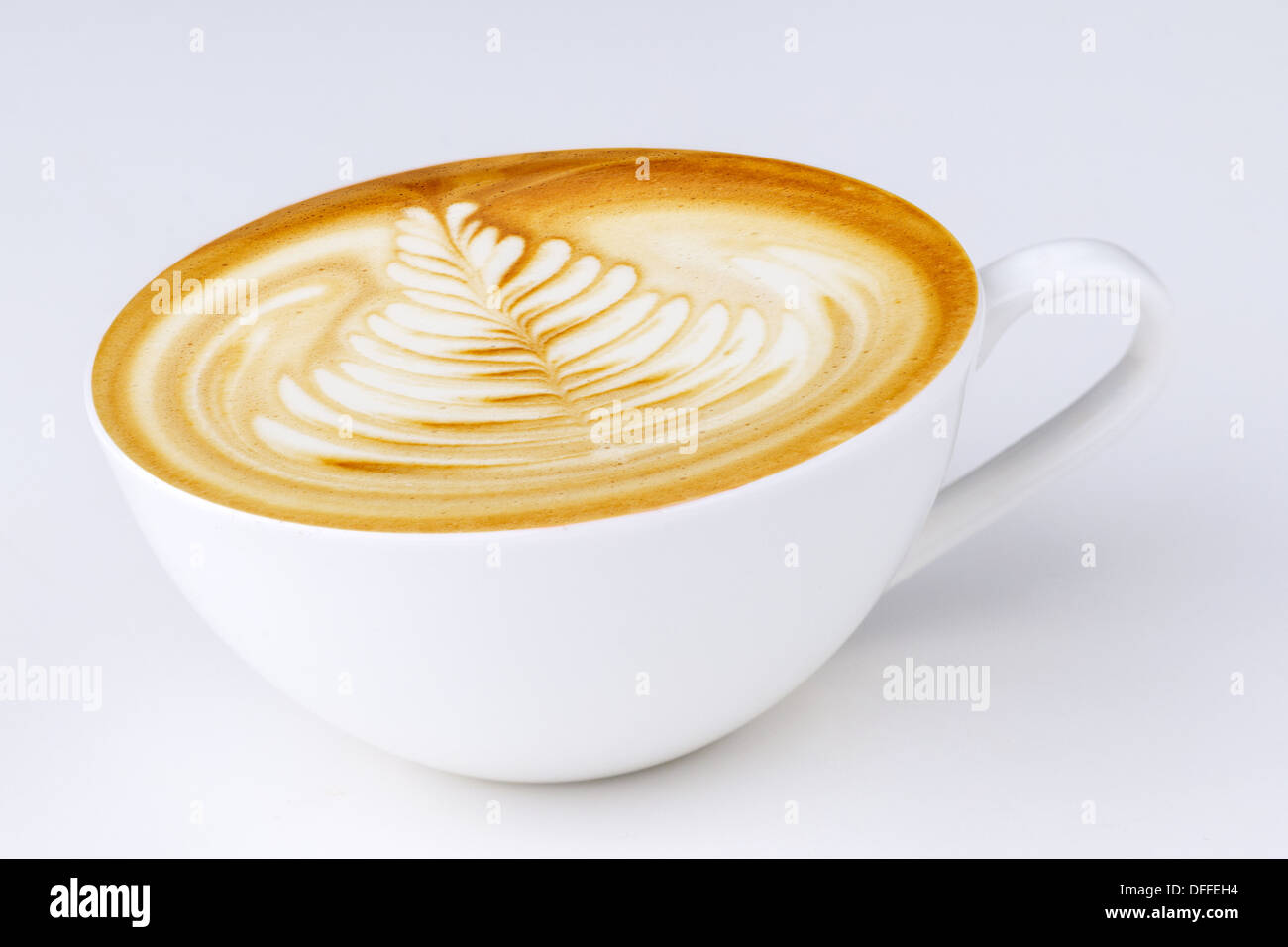 Cappuccino in a white cup on a white background - Stock Image