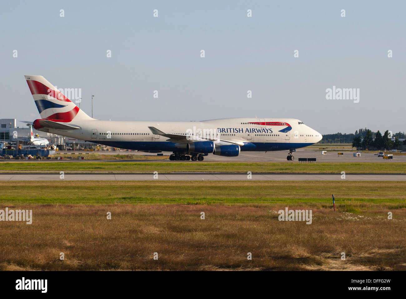 British Airways Boeing 747-436 taxiing down runway at YVR, Vancouver International Airport. - Stock Image
