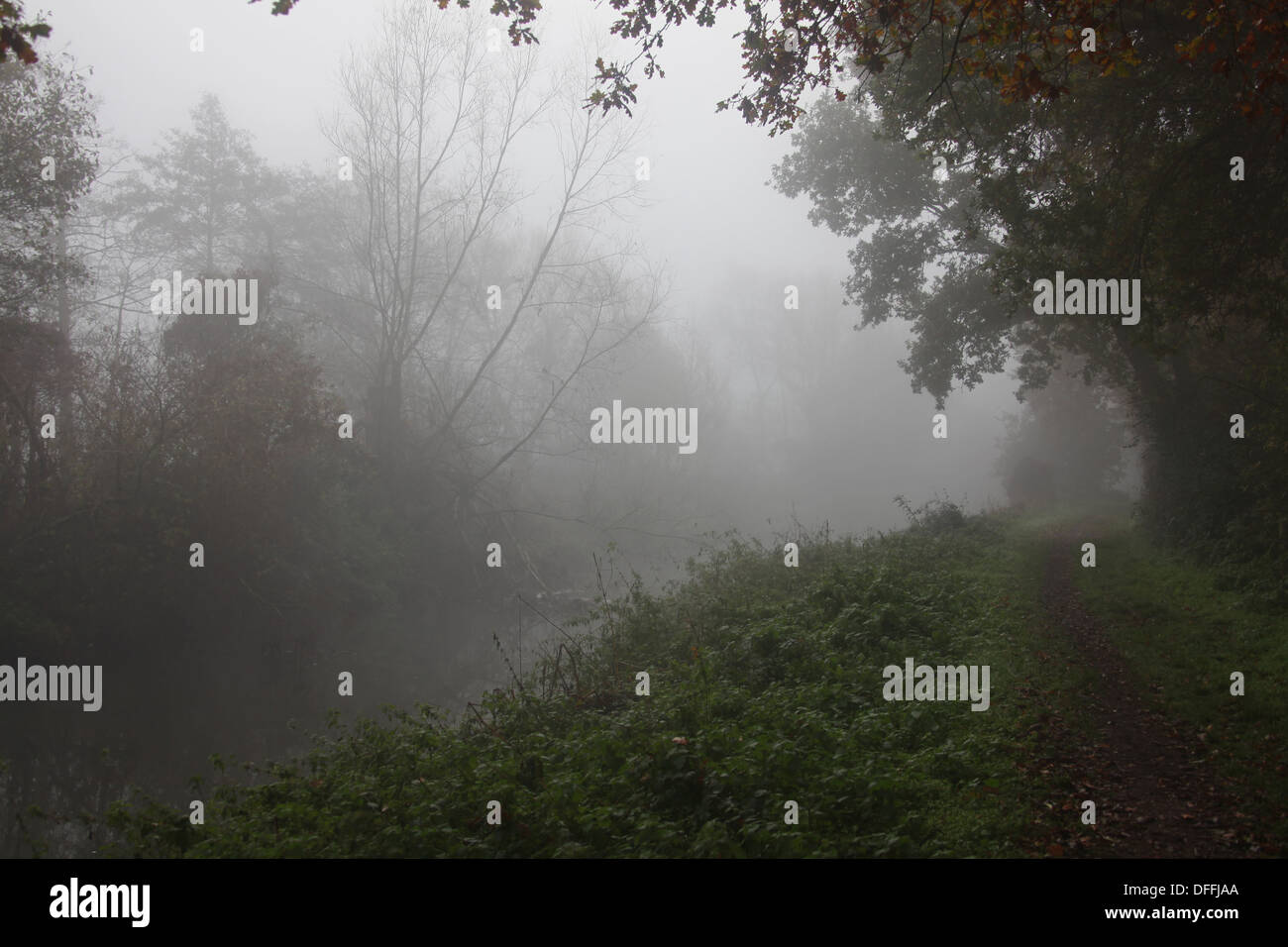 A misty morning alongside a cold and unwelcome looking river showing a footpath cloaked in mist. - Stock Image