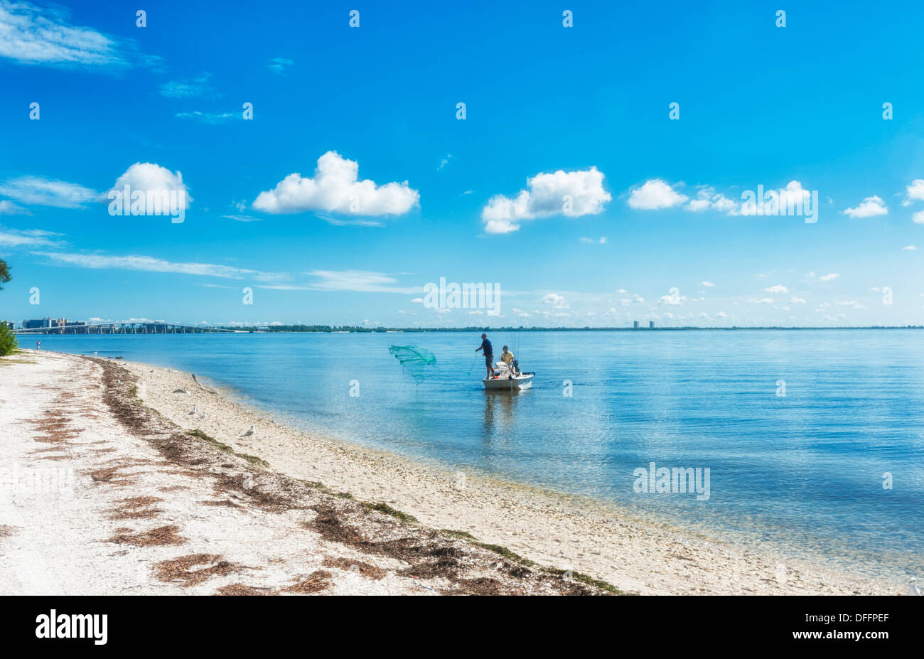 Two men fishing at distance cast net into blue water of the Gulfcoast of Florida blue skies few clouds. White sandy Stock Photo