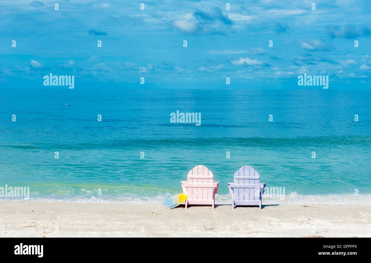 Two pastel wooden chairs on the sand on a tropical beach facing the ocean watching waves roll in. Blue sky turquoise Stock Photo