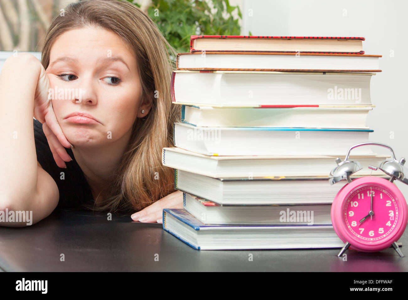 A young woman glances at the large pile of books for exam study a young woman glances at the large pile of books for exam study time ticks by reminding her of the limited time to prepare altavistaventures Image collections