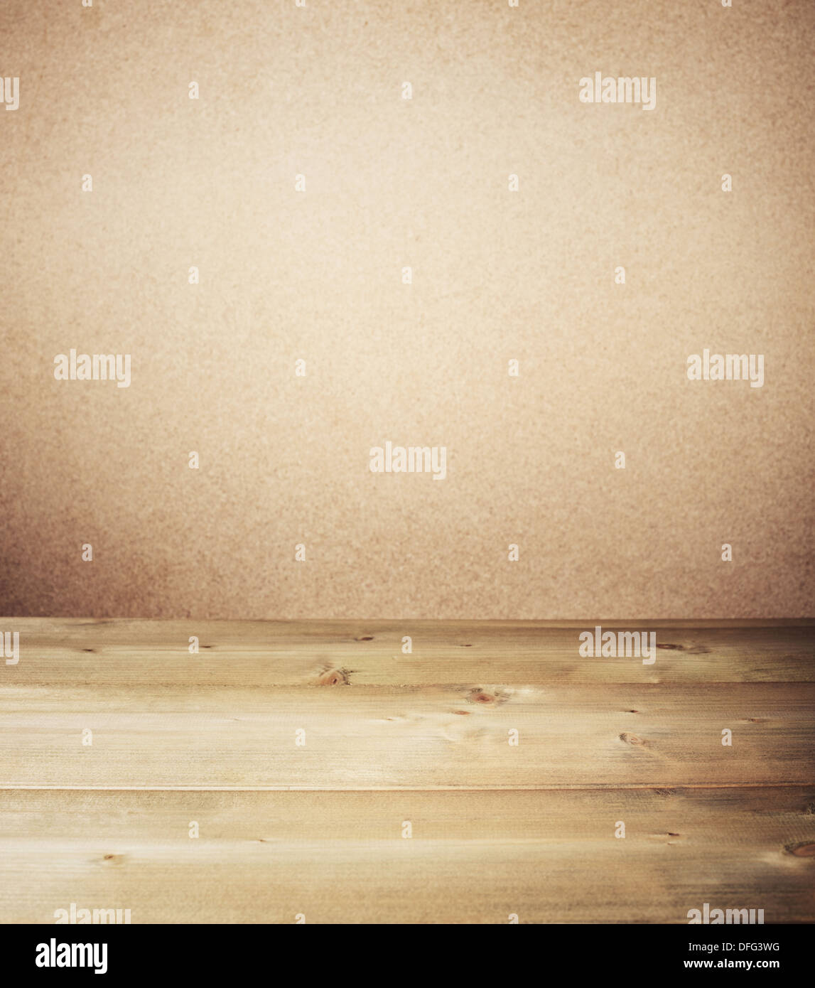 Wooden table in front of wall.  - Stock Image