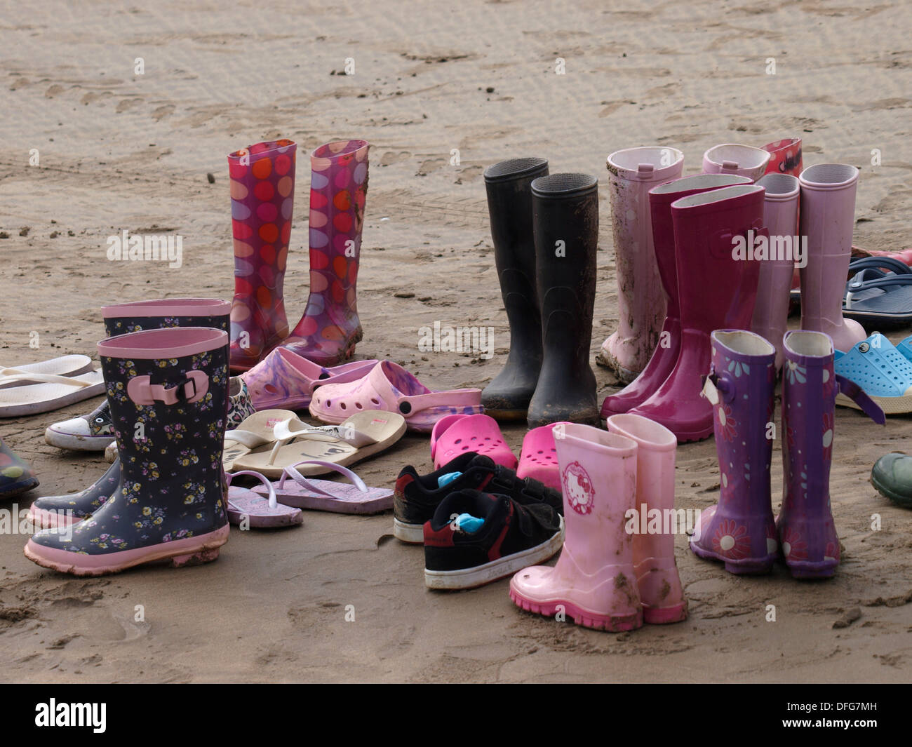 Collection of shoes and wellie boots on the beach, UK - Stock Image