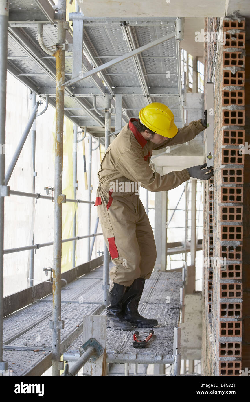 Worker with spirit level on scaffold, housing construction. Guipuzcoa, Euskadi, Spain - Stock Image