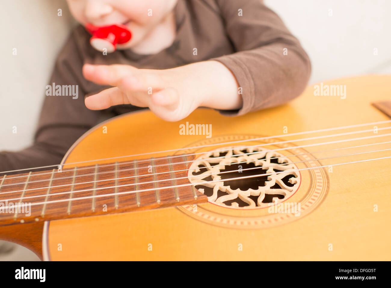 Young girl, 4 years old, playing with an acoustic guitar. - Stock Image