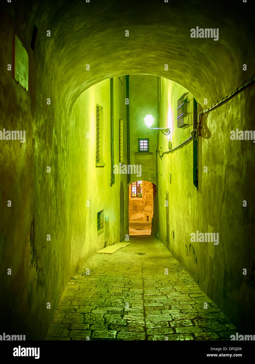Picture of a narrow illuminated alley in Volterra, Italy - Stock Image