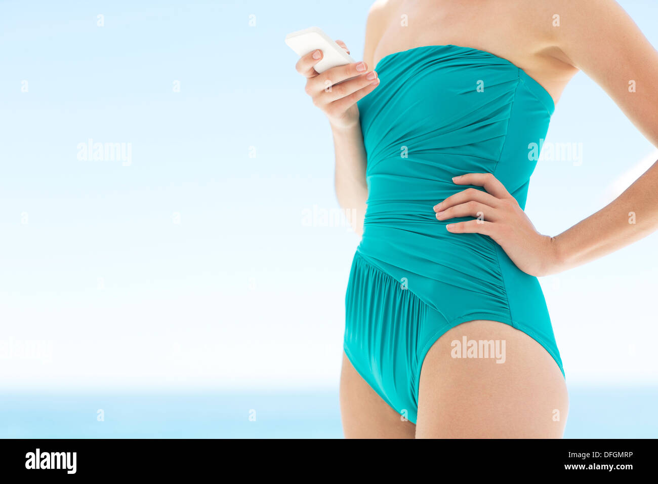 Woman in bathing suit using cell phone - Stock Image