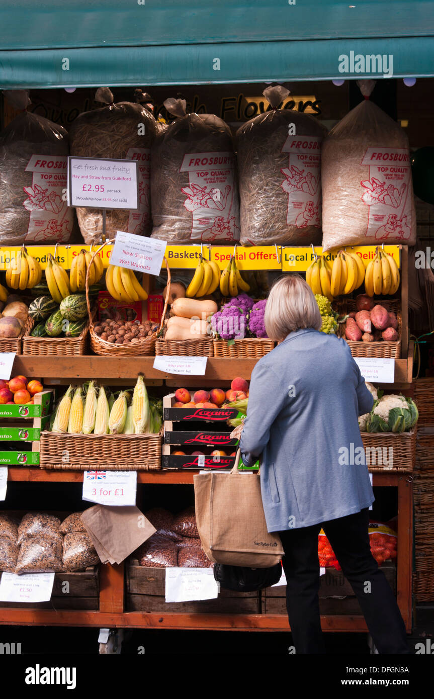 Housewife Browsing Outside A greengrocers Fruit and Veg Shop Display UK - Stock Image