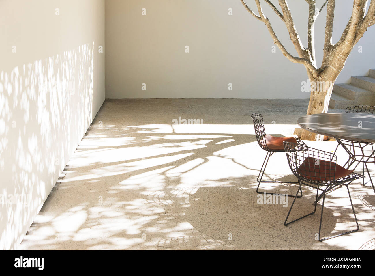 Table and chairs casting shadows in courtyard Stock Photo