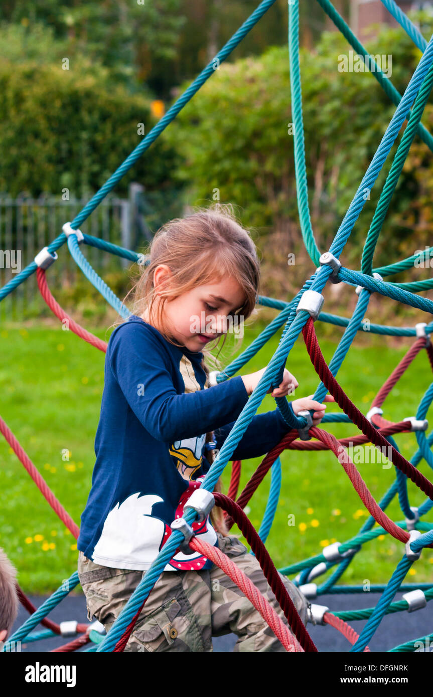 Little Girl Climbing Up A Rope Climbing Frame At A Childrens Stock ...