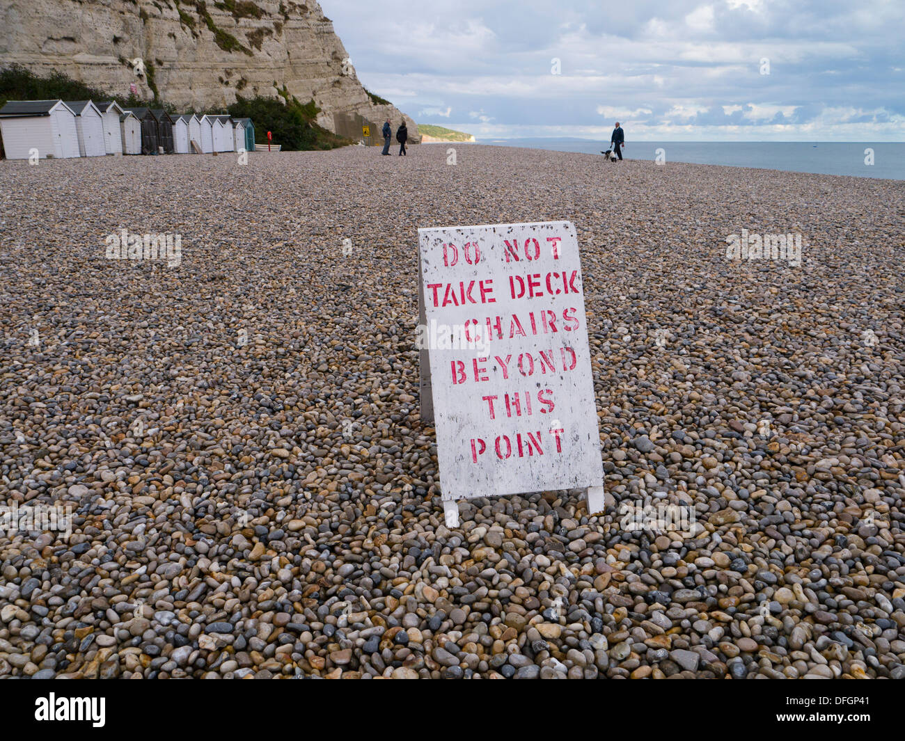 Deck chair sign on shingle beach at Beer, Devon, England, UK - Stock Image