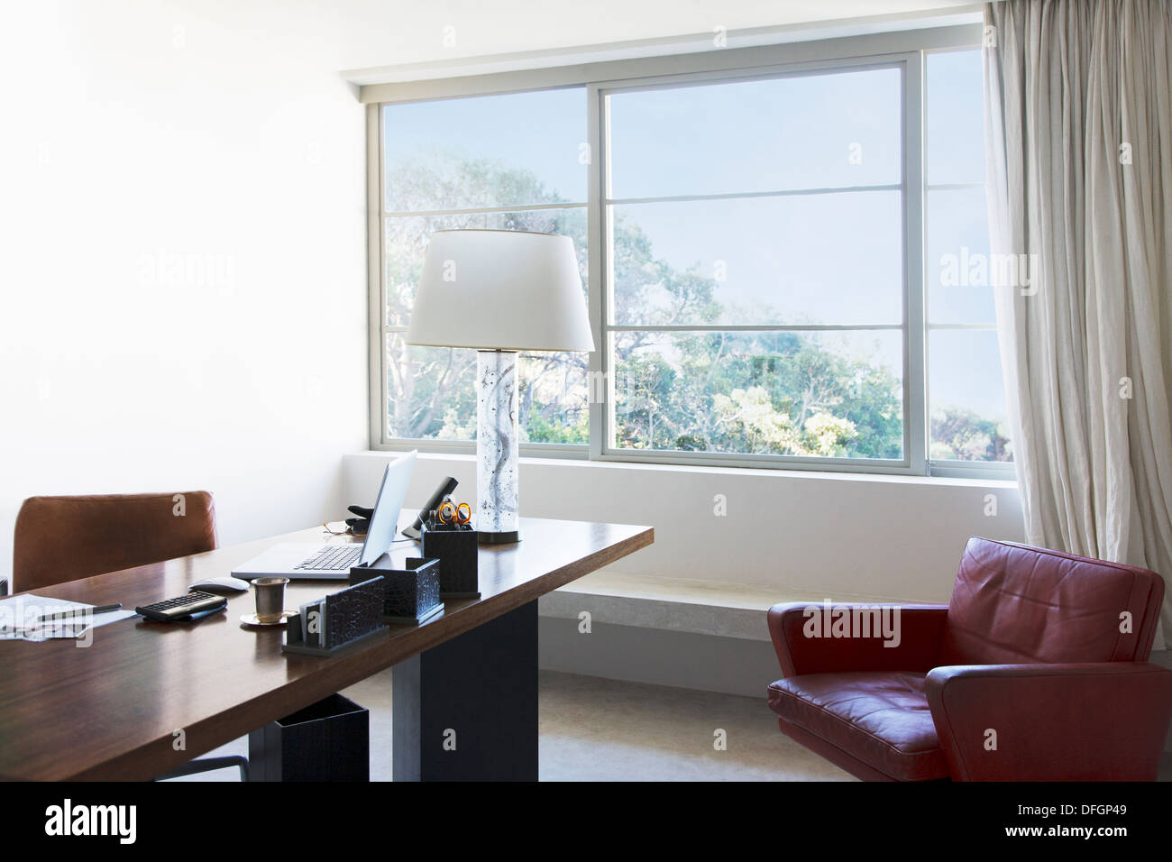 Laptop and lamp on desk in office - Stock Image