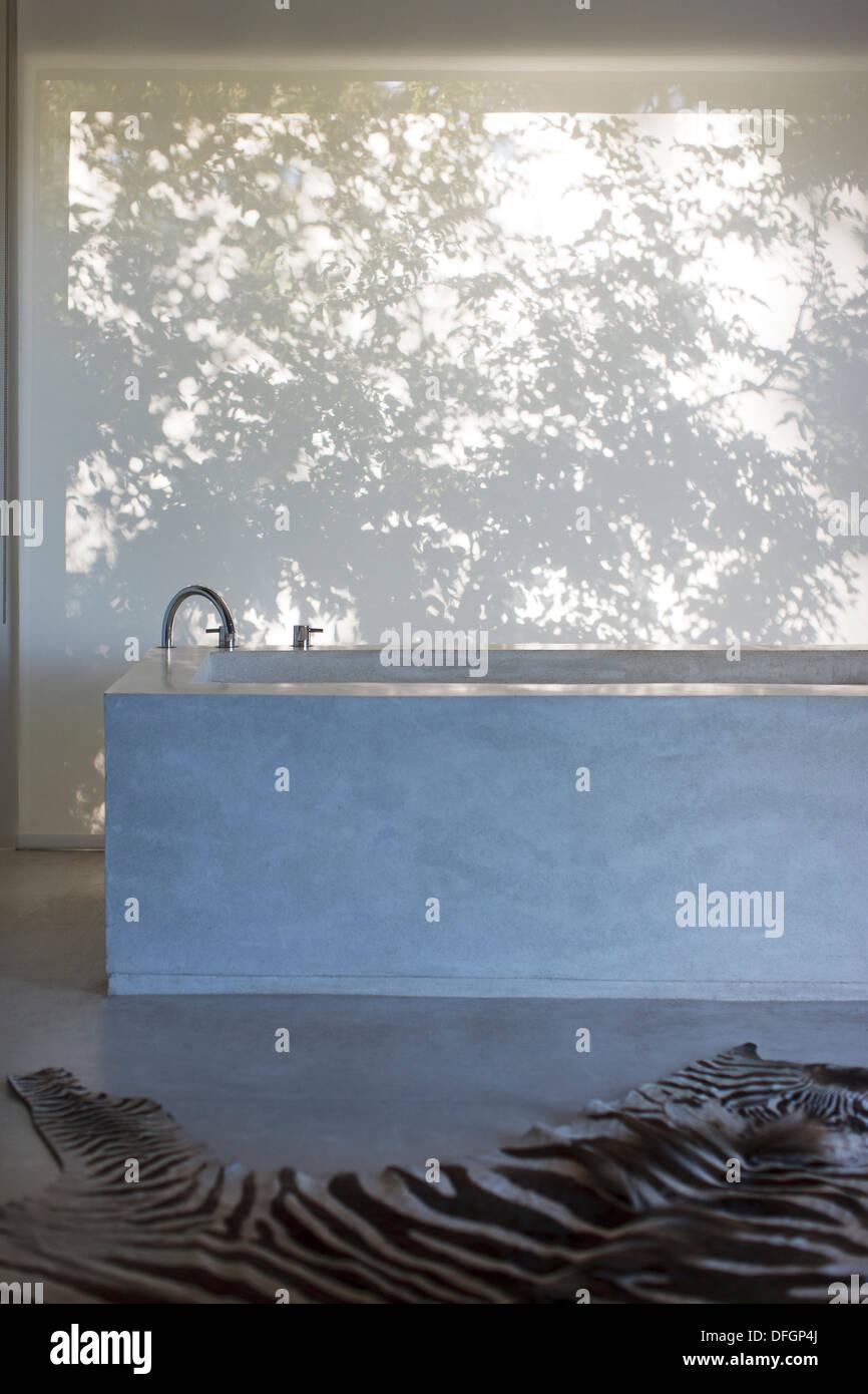 Bathtub and zebra print rug in modern bathroom - Stock Image
