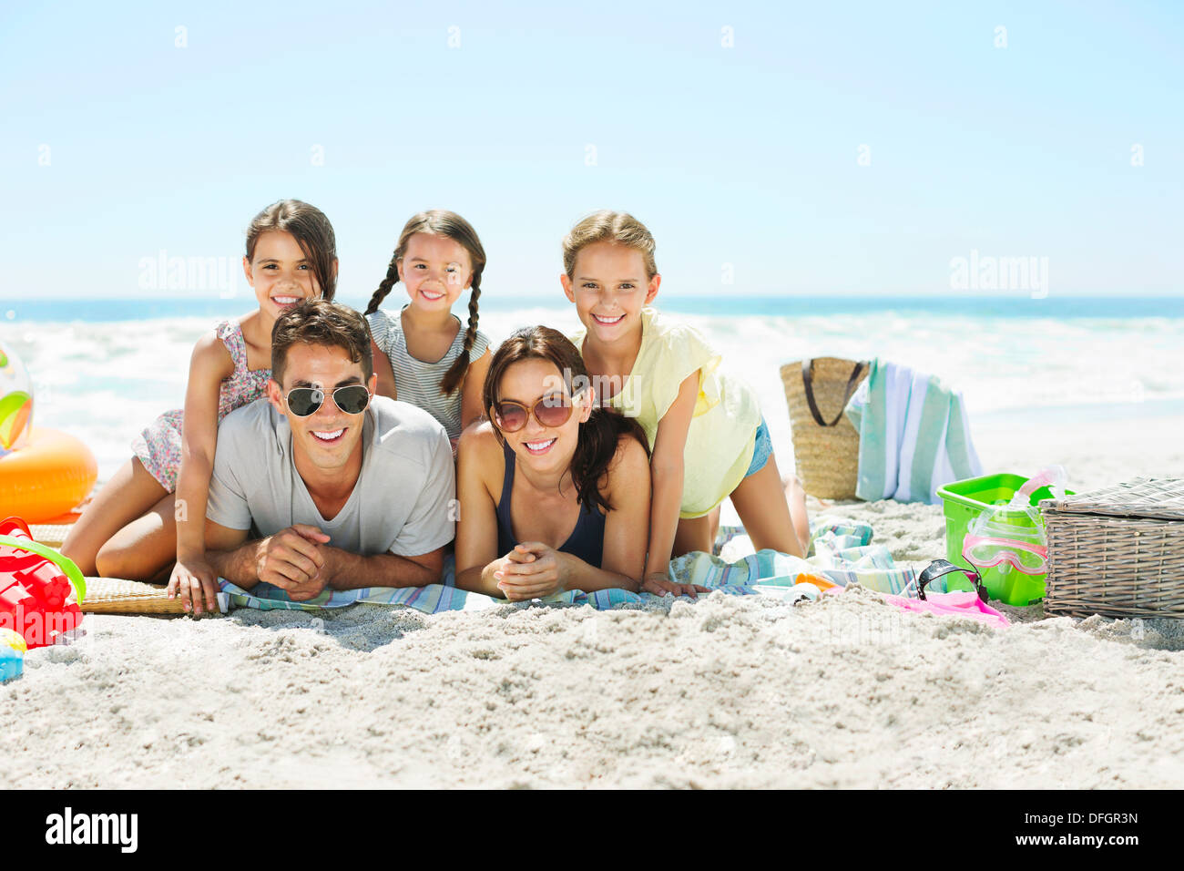 Portrait of smiling family on beach - Stock Image