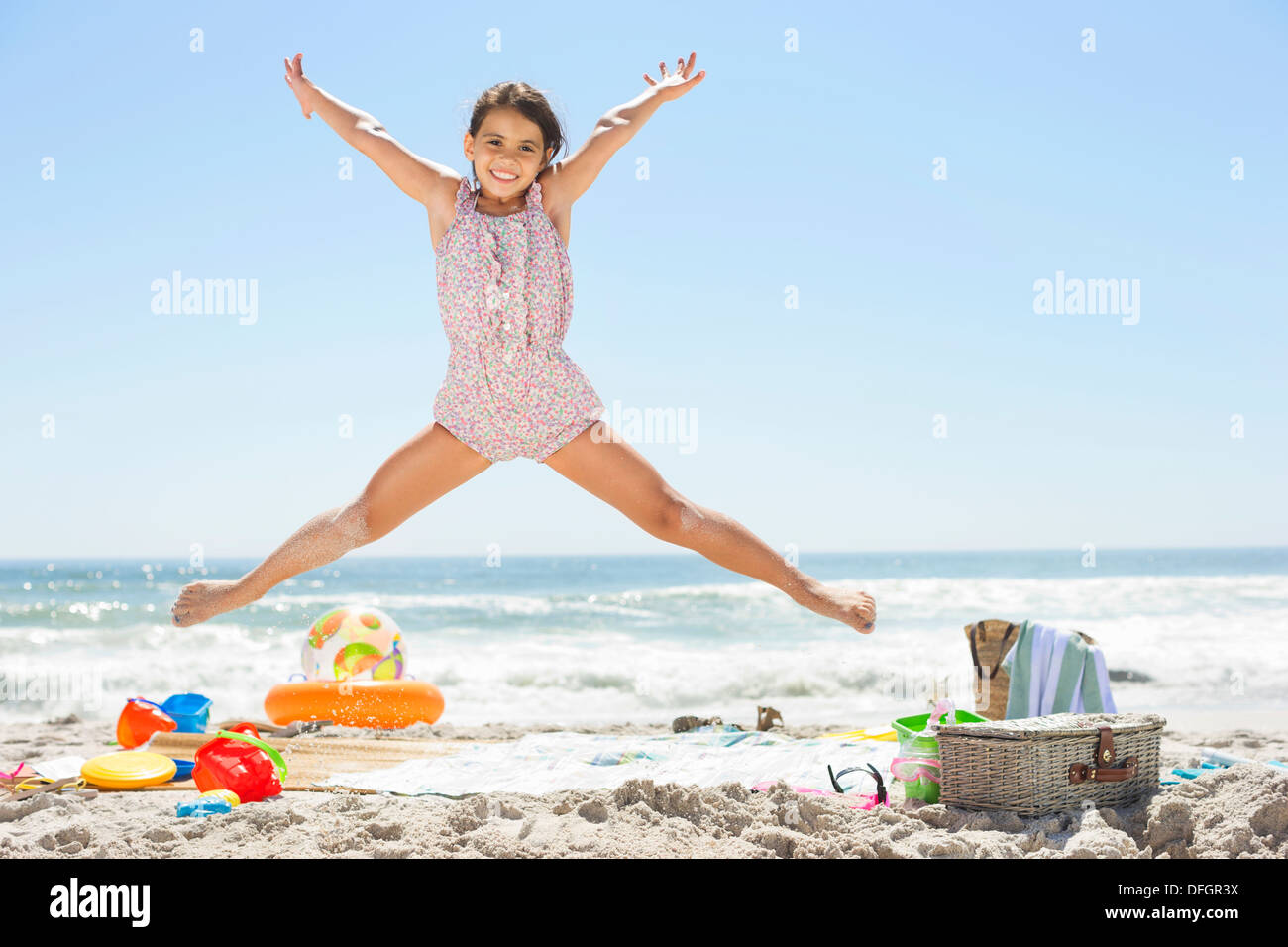 Girl jumping on beach - Stock Image