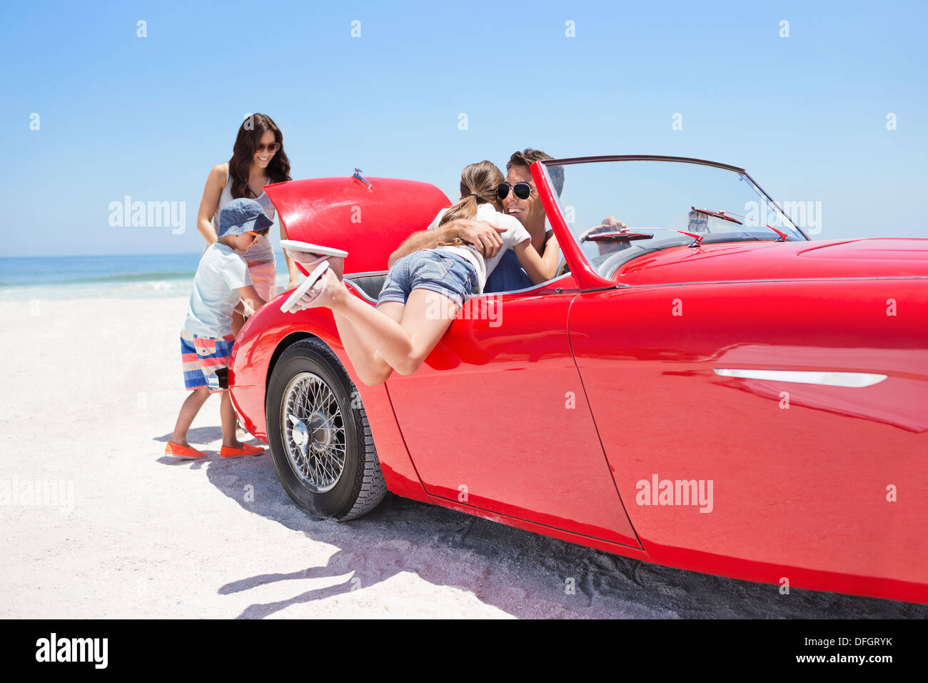 Family packing convertible on beach Stock Photo