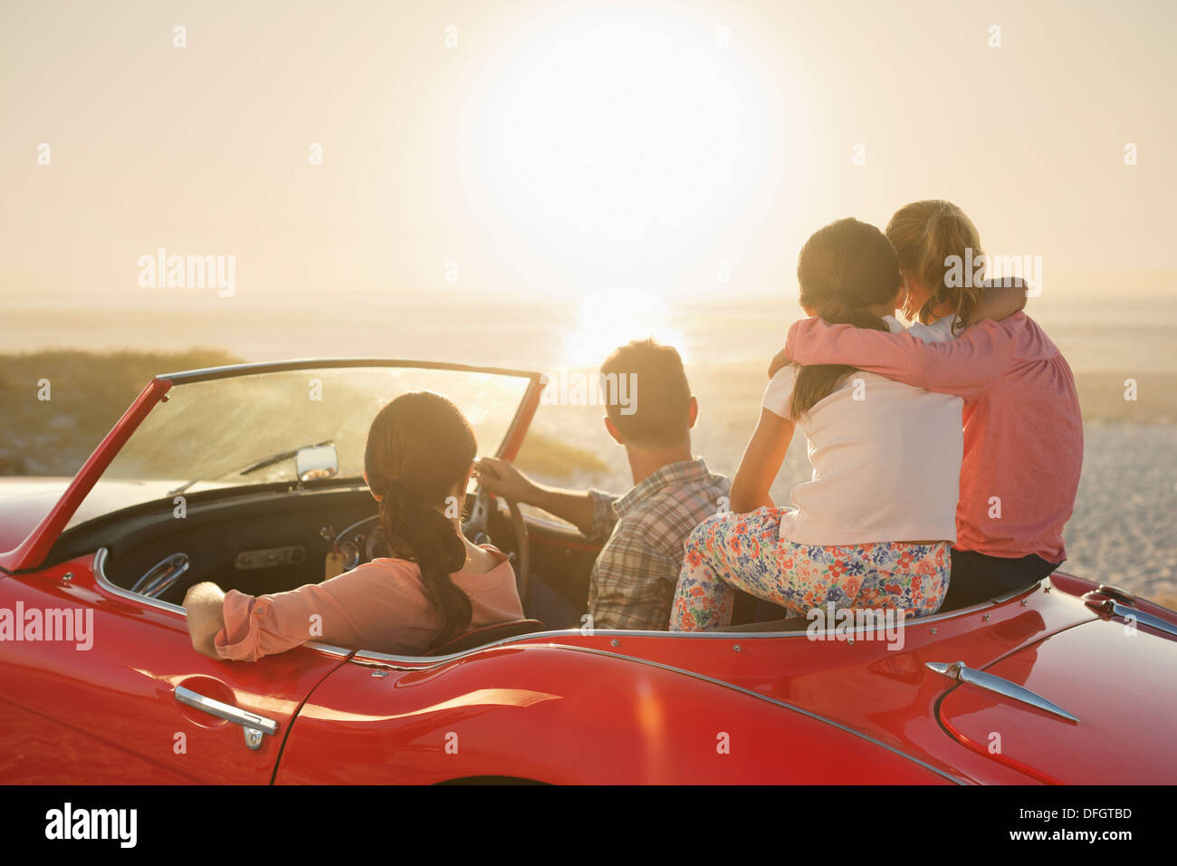 Family watching sunset over ocean from convertible on beach - Stock Image