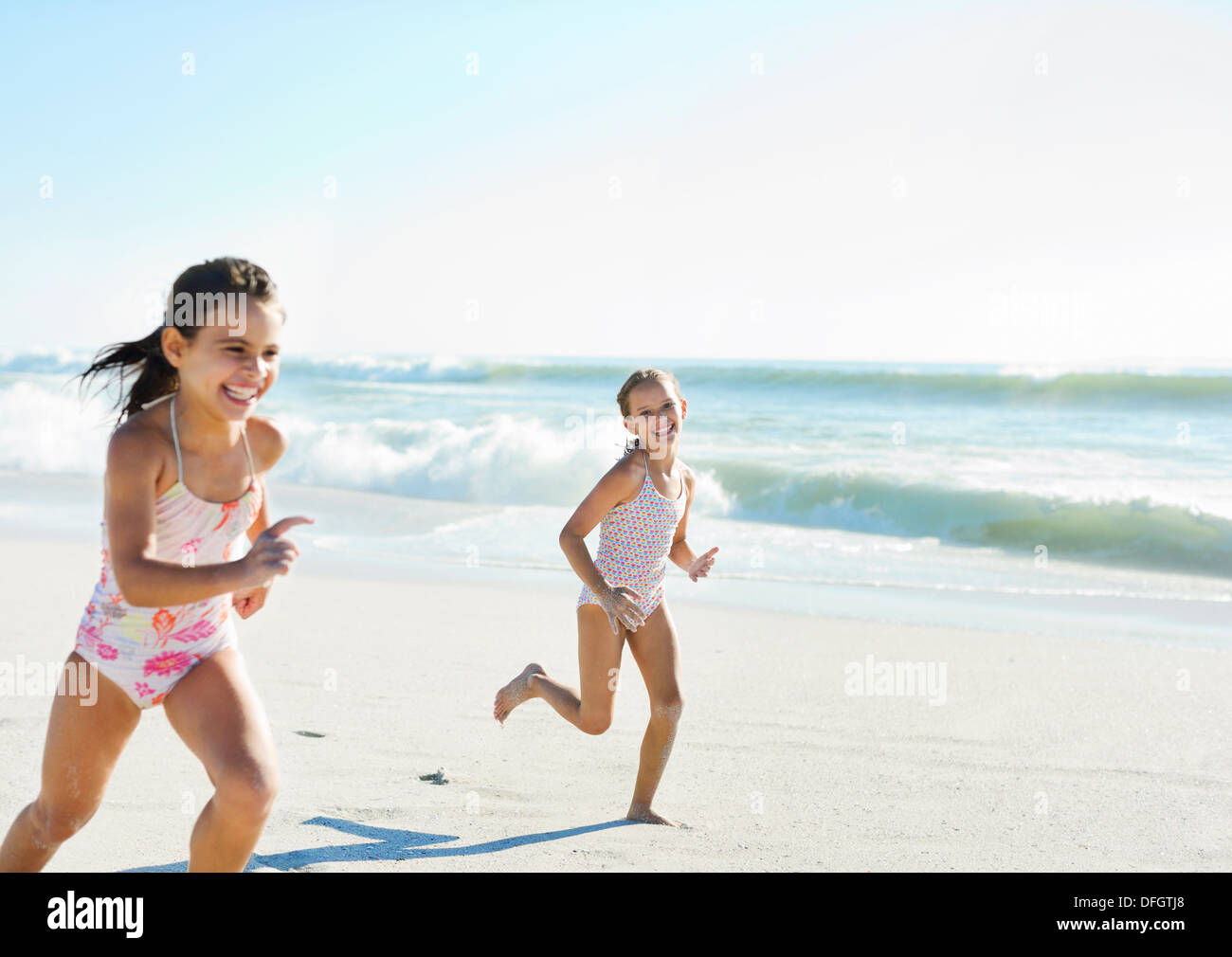 Girls running on beach - Stock Image