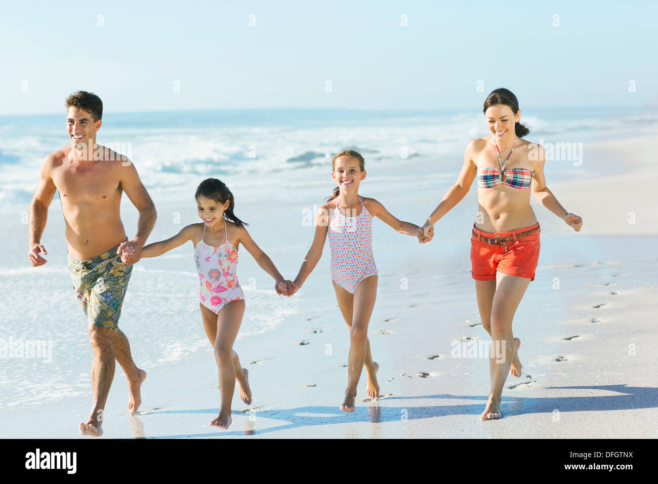 Family holding hands and running on beach - Stock Image