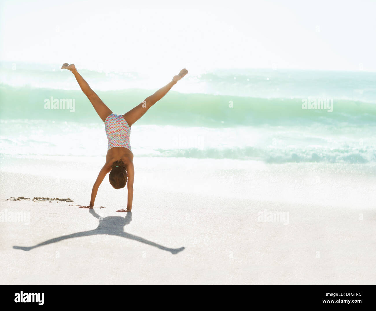 Girl doing cartwheel on beach - Stock Image