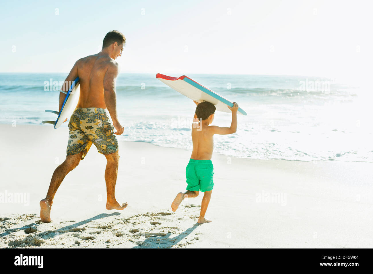 Father and son carrying surfboard and bodyboard on beach - Stock Image
