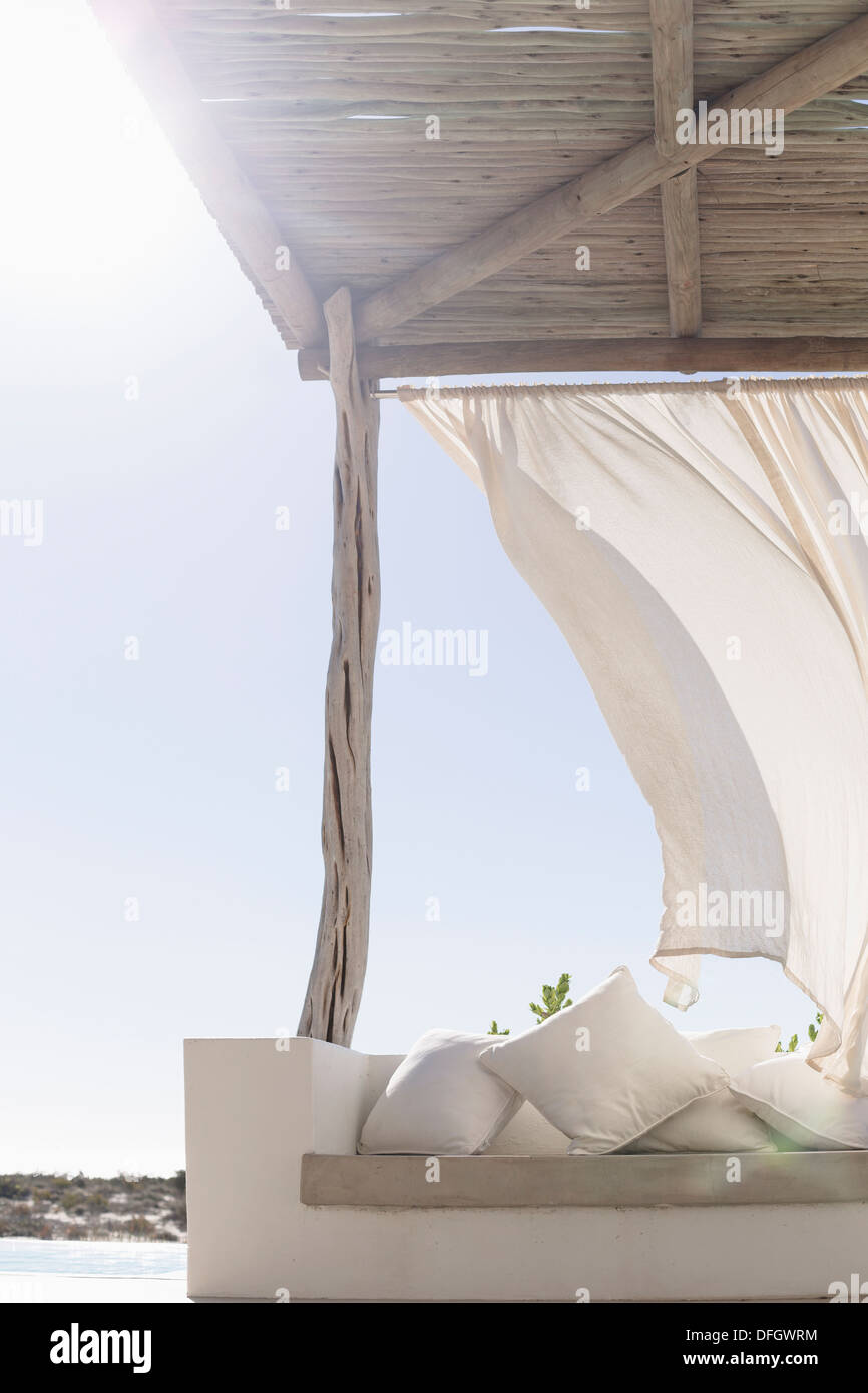 Wind blowing curtain on sunny patio - Stock Image