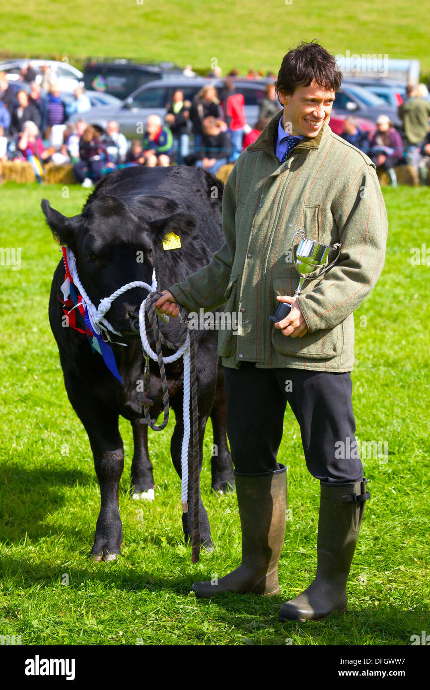 Rory Stewart Conservative Member of Parliament for Penrith and the Border. Leading at cow holding a cup at Hesket Newmarket Show - Stock Image