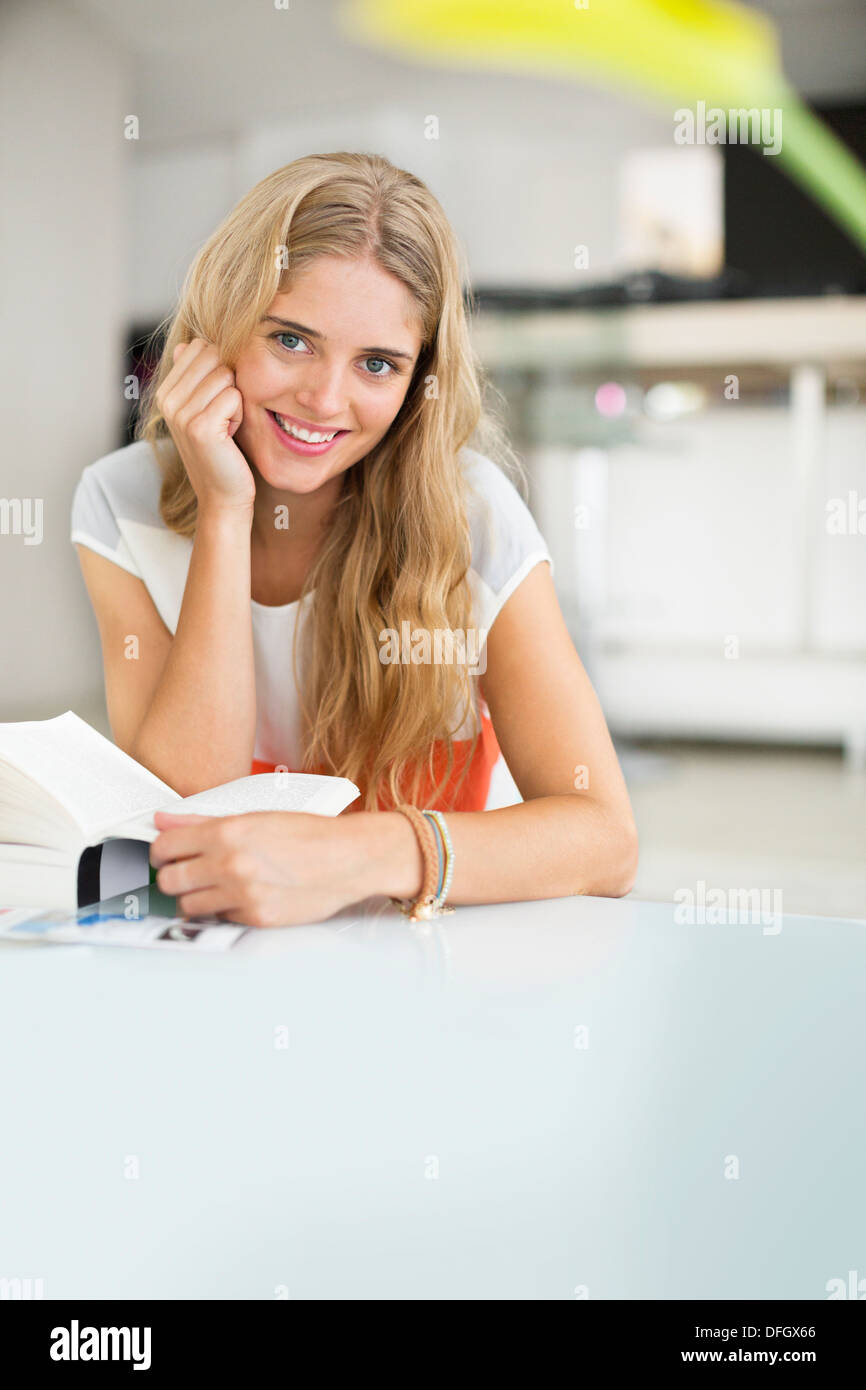 Woman reading book at table - Stock Image