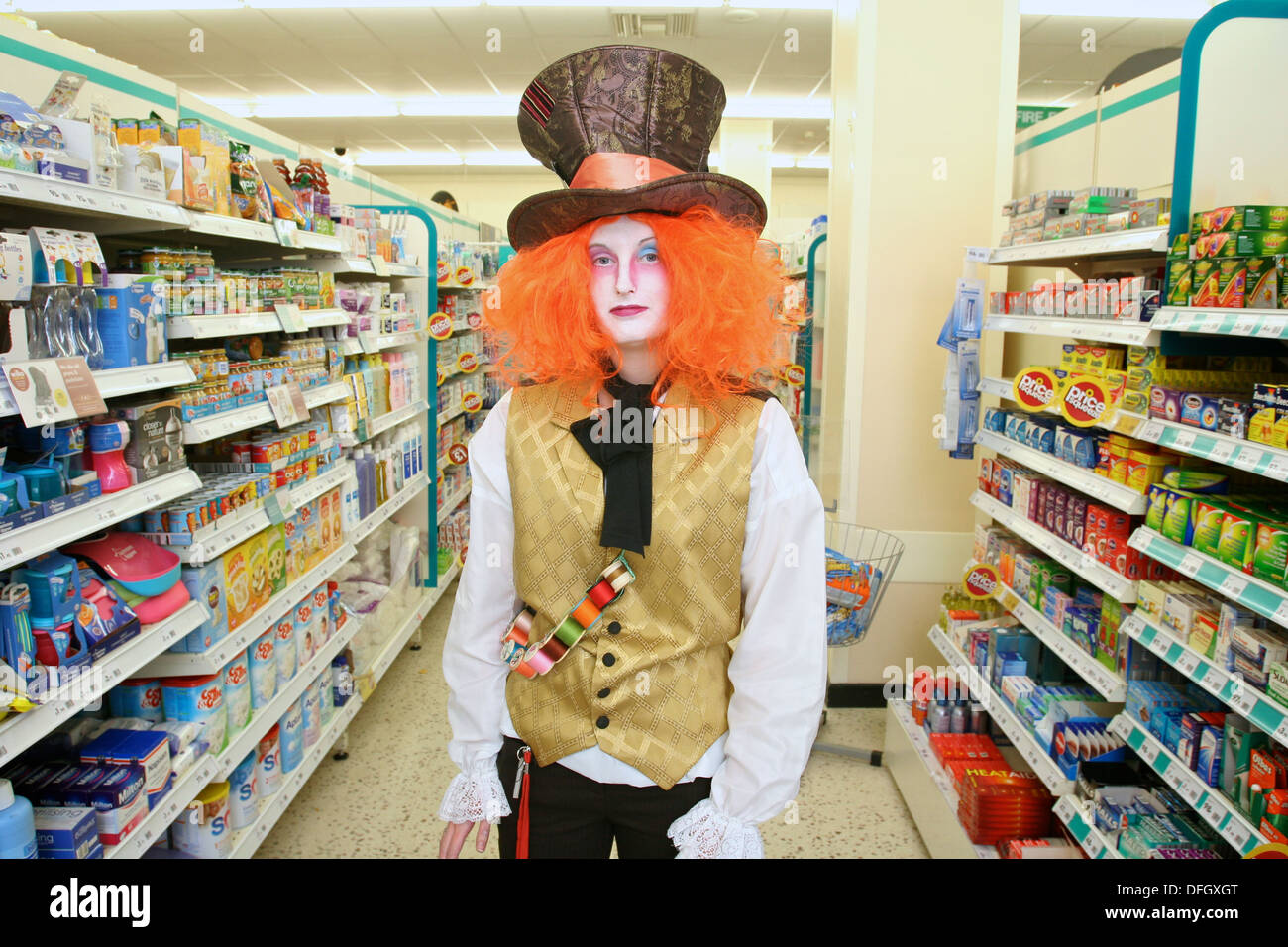 Supermarket attendant in Halloween fancy dress costume as 'The Hatter' from Alice's Adventures in Wonderland. UK - Stock Image