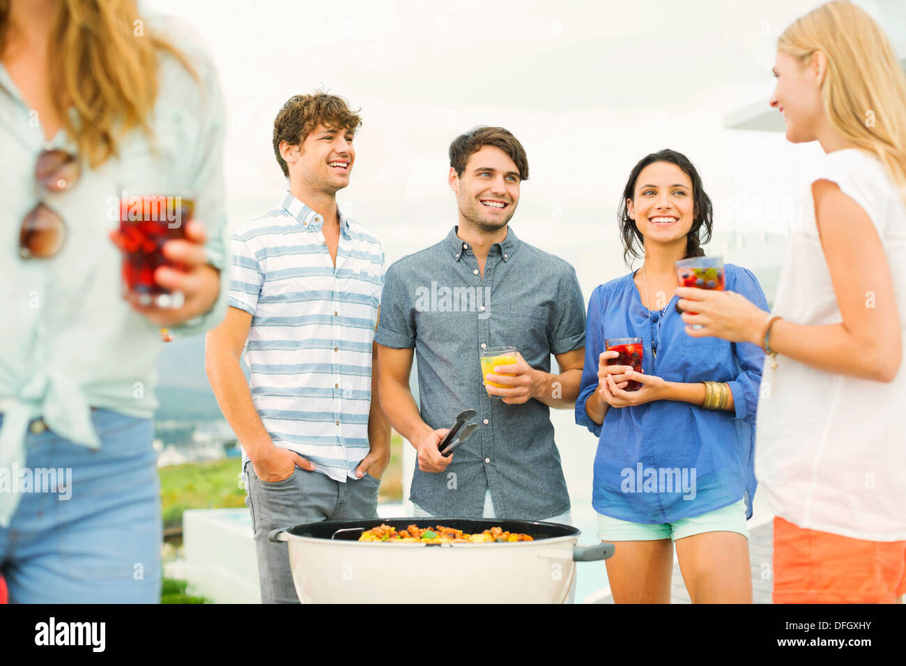 Friends enjoying drinks at barbecue - Stock Image