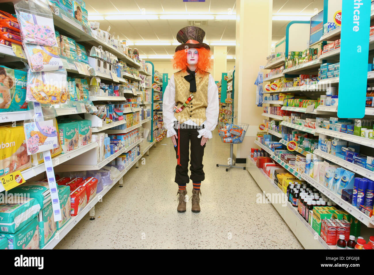 Supermarket attendant dressed in Halloween fancydress costume as 'The Hatter' from Alice's Adventures in Wonderland. UK - Stock Image