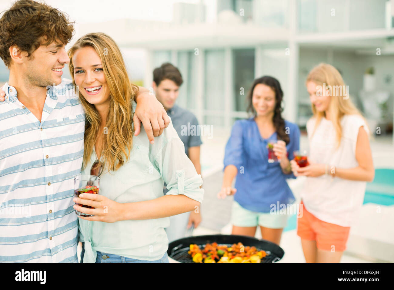 Couple hugging at barbecue - Stock Image