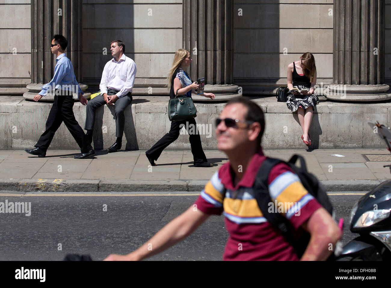 A man sleeps in the sunshine during hot weather leaning against the Bank of England in London on July 9, 2013. - Stock Image