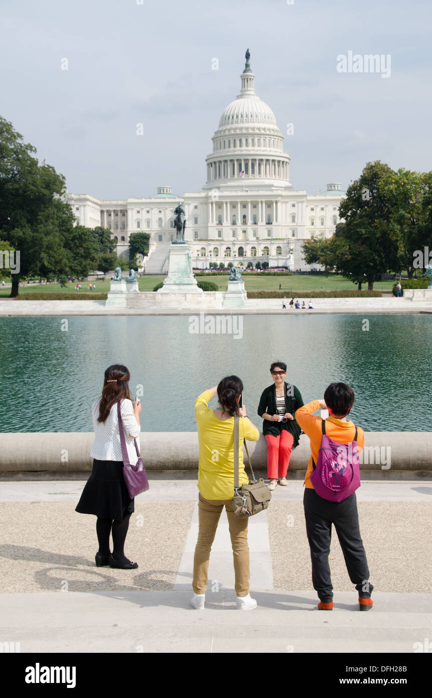 Asian tourists pose for pictures in front of the U.S. Congress during the budget shutdown of October 2013. - Stock Image