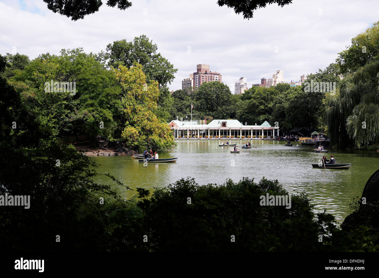Looking at the Central Park Boathouse, People in Rowboats on the Lake, New York City - Stock Image