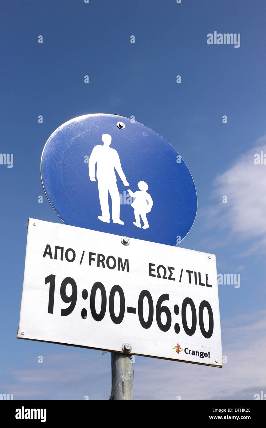 A sign in Greek denoting a pedestrianized area and the times that apply. - Stock Image